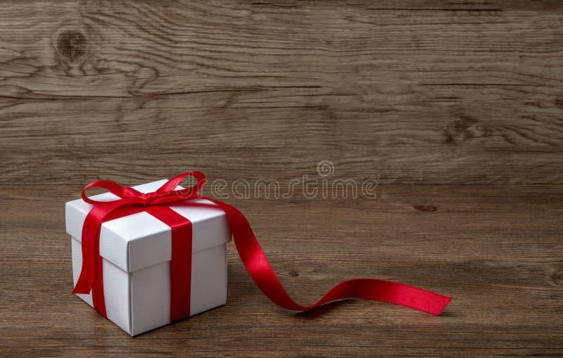 Caixa de presente com curva vermelha na tabela rústica, no Natal ou em uma outra celebração foto de stock