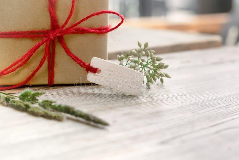 Caixa de presente com etiqueta vazia e flor na tabela de madeira, espaço da cópia para texting imagem de stock