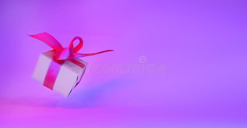 Caixa de presente com a fita vermelha no fundo de néon na moda da cor bandeira da gravidade zero levitation Copyspace Vendas do c foto de stock royalty free