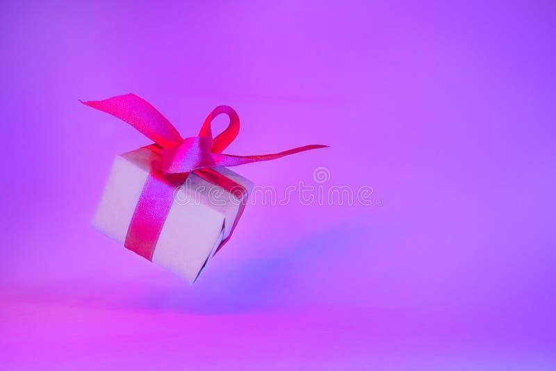 Caixa de presente com a fita vermelha no fundo de néon na moda da cor Gravidade zero levitation Copyspace Vendas do conceito, pre fotos de stock royalty free