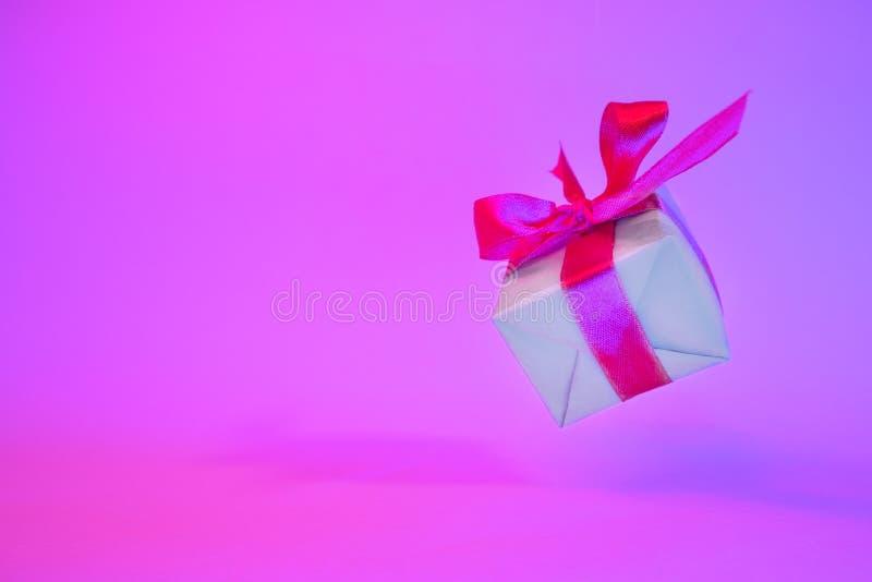 Caixa de presente com a fita vermelha no fundo de néon na moda da cor Gravidade zero levitation Copyspace Vendas do conceito, pre foto de stock royalty free