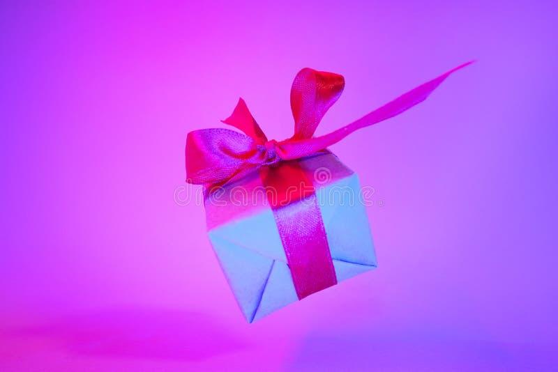 Caixa de presente com a fita vermelha no fundo de néon na moda da cor Gravidade zero levitation Copyspace Vendas do conceito, pre imagem de stock royalty free