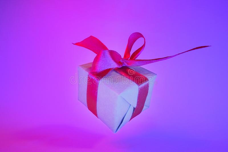 Caixa de presente com a fita vermelha no fundo de néon na moda da cor Gravidade zero levitation Copyspace Vendas do conceito, pre fotos de stock