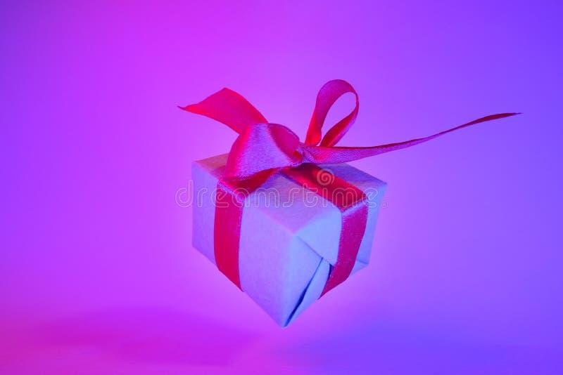 Caixa de presente com a fita vermelha no fundo de néon na moda da cor Gravidade zero levitation Copyspace Vendas do conceito, pre imagens de stock royalty free
