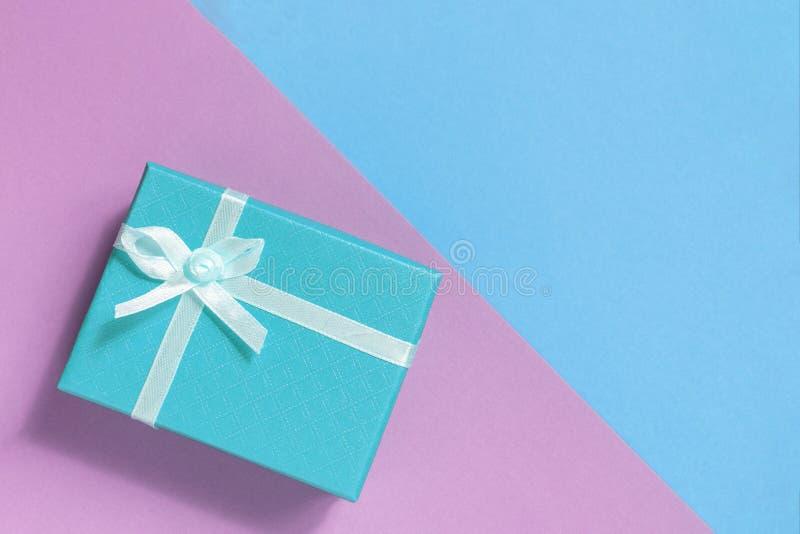 Caixa de presente com uma curva de claro - cor azul em um rosa e fundo azul imagens de stock
