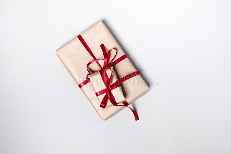 Caixa de presente com uma fita vermelha em um fundo branco Vista superior, lisa foto de stock