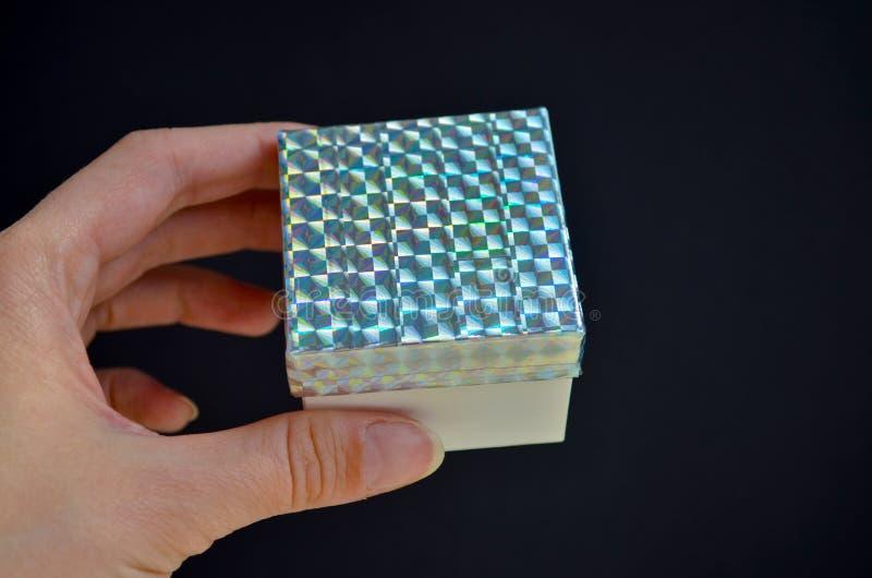 Caixa de presente com uma tampa do arco-íris na mão fêmea no fundo preto Ideia de DIY como decorar um presente com uma fita color imagem de stock royalty free