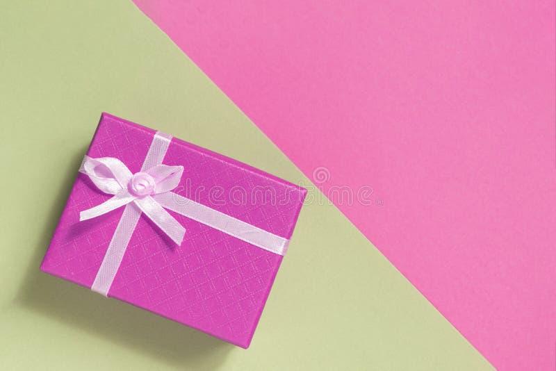 Caixa de presente cor-de-rosa com curva Fundo cor-de-rosa amarelo com caixa de presente Vista superior foto de stock royalty free