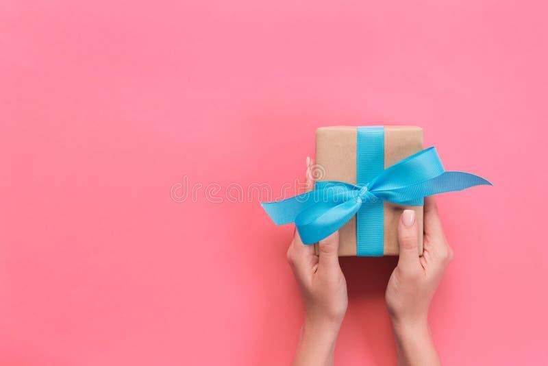 Caixa de presente da terra arrendada de braços da mulher com a fita azul no fundo da cor, vista superior fotos de stock royalty free