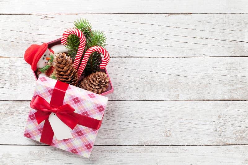 A caixa de presente do Natal com bastão de doces e o boneco de neve brincam fotografia de stock
