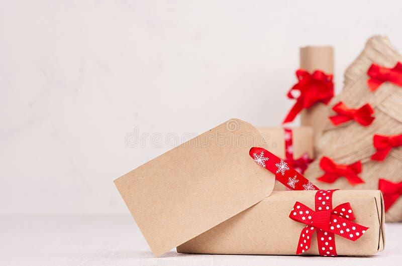 Caixa de presente do Natal com etiqueta de cumprimento vazia e close up vermelho da curva e da fita na placa de madeira branca co fotos de stock