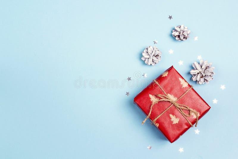 Caixa de presente do Natal com os cones no fundo azul fotos de stock royalty free