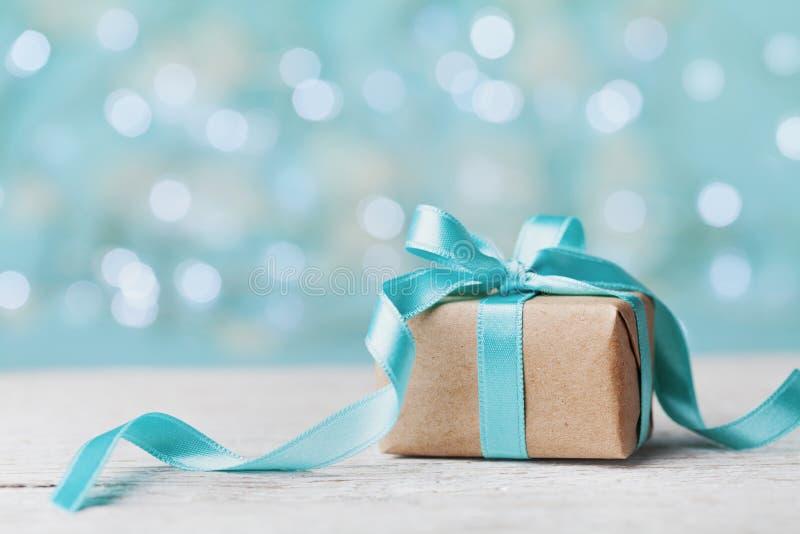 Caixa de presente do Natal contra o fundo do bokeh de turquesa Cartão do feriado fotografia de stock royalty free
