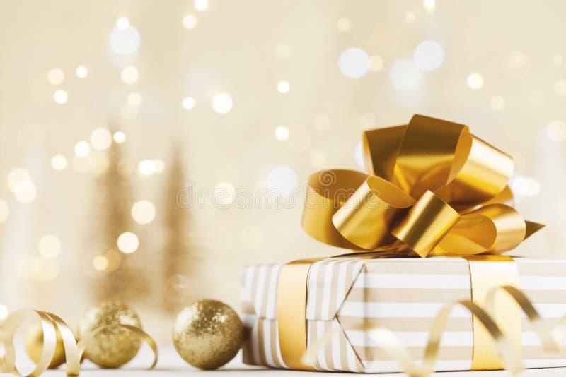 Caixa de presente do Natal contra o fundo dourado do bokeh Cartão do feriado fotos de stock