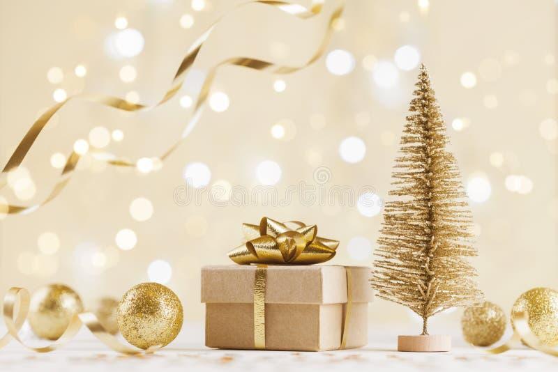 Caixa de presente do Natal contra o fundo dourado do bokeh Cartão do feriado foto de stock royalty free