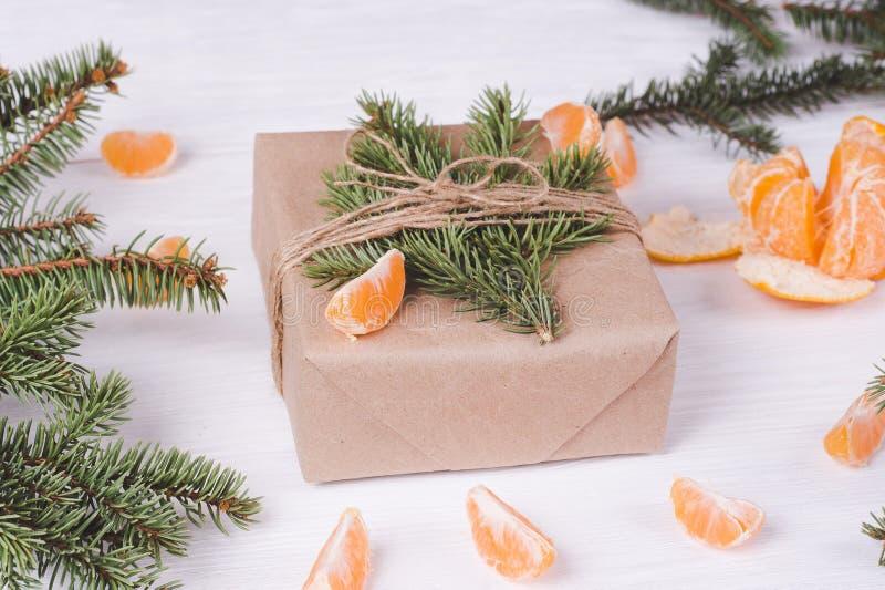 Caixa de presente do Natal em um fundo de madeira branco e em tangerinas Atributos do ` s do ano novo imagens de stock