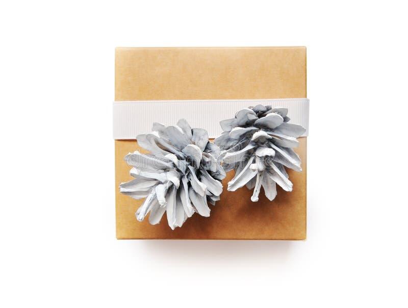 A caixa de presente do Natal envolvida no papel reciclado marrom com cone e a fita branca curvam a vista superior isolada no fund fotografia de stock royalty free