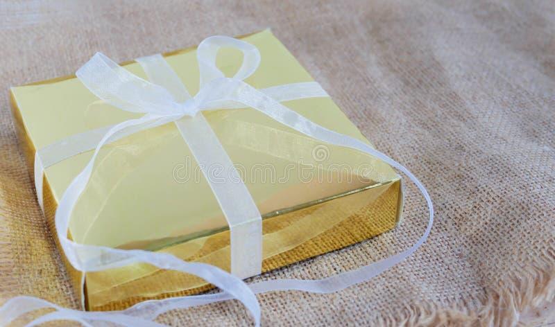 Caixa de presente do ouro com a fita branca no saco marrom fotografia de stock royalty free