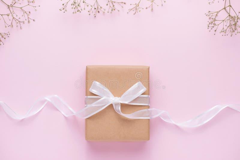 Caixa de presente do papel de embalagem amarrada com fita cor-de-rosa e as flores brancas para imagem de stock