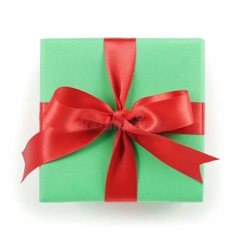 Caixa de presente do papel verde com opinião superior da curva vermelha da fita no fundo branco imagens de stock