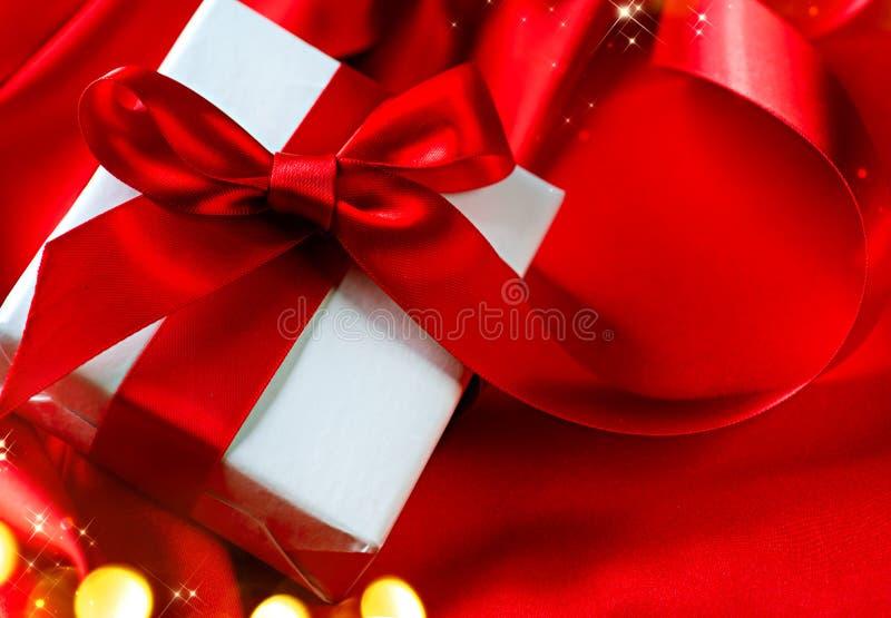 Caixa de presente do Valentim no fundo de seda vermelho imagem de stock royalty free