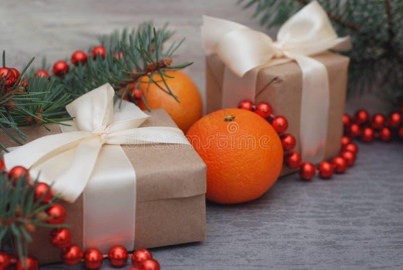 Caixa de presente dos anos novos do Natal com curva vermelha da fita Ramos de árvore do abeto das nozes dos cones do pinho das ta fotografia de stock