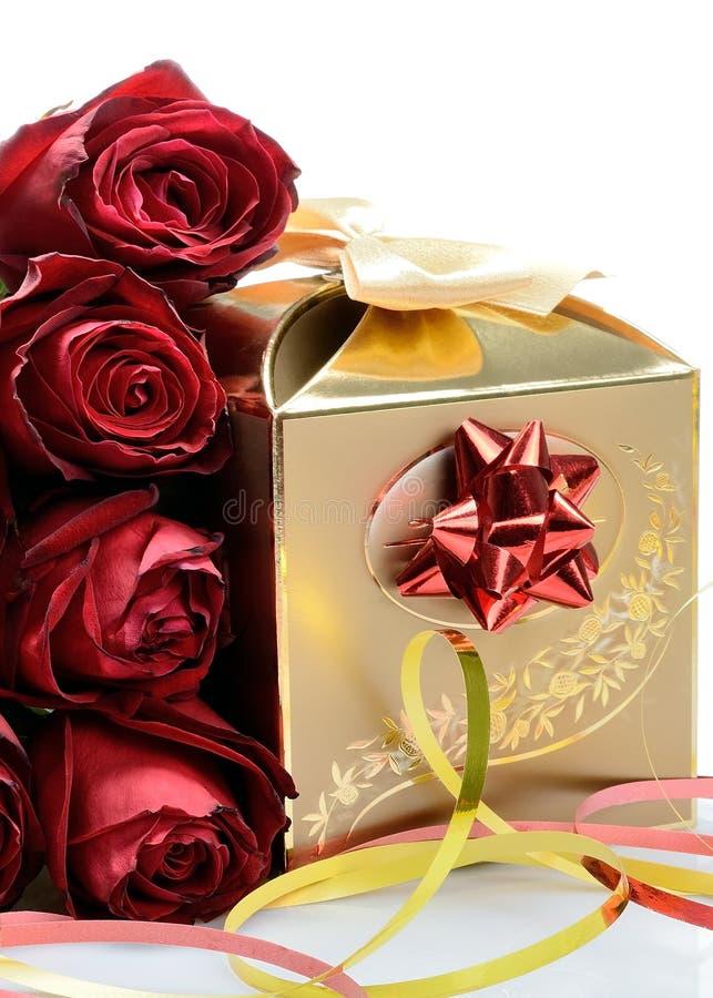 Caixa de presente dourada para o feriado e rosas vermelho-marrons das flores em um fundo branco imagem de stock royalty free
