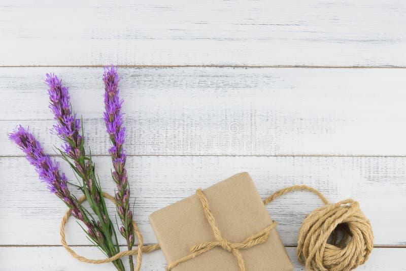 A caixa de presente e a corda de Brown decoradas com liatris violeta florescem imagens de stock royalty free