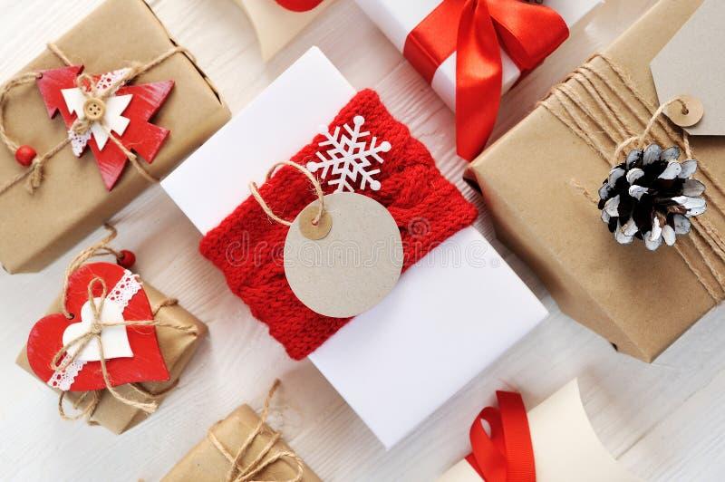 A caixa de presente e a etiqueta vermelhas do Natal do modelo com papel vazio etiquetam e fita e curva decorativas Configuração l fotos de stock