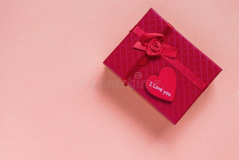 A caixa de presente e o coração vermelhos com texto amam-no em um fundo cor-de-rosa Copie o espa?o imagens de stock royalty free
