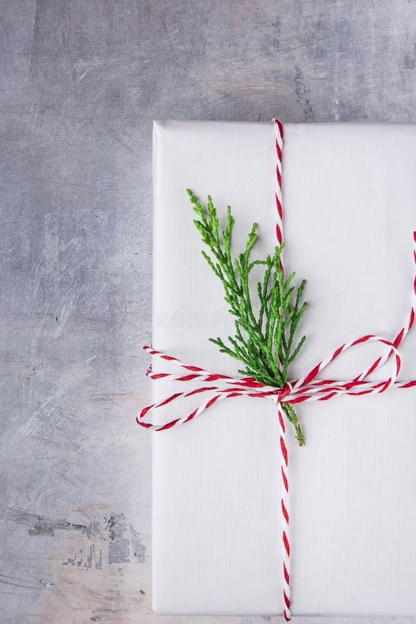 Caixa de presente elegante envolvida no Livro Branco amarrado com o galho vermelho do zimbro do verde da fita Venda de compra dos fotografia de stock royalty free