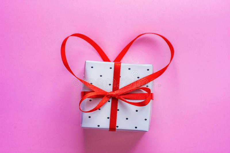 Caixa de presente elegante pequena amarrada com a fita vermelha com curva na forma do coração no fundo cor-de-rosa Valentine Gree imagem de stock royalty free