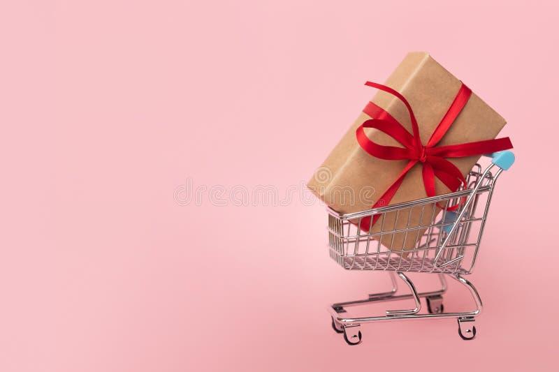 Caixa de presente em um carrinho de compras no fundo cor-de-rosa Conceito para compras Copie o espaço foto de stock royalty free