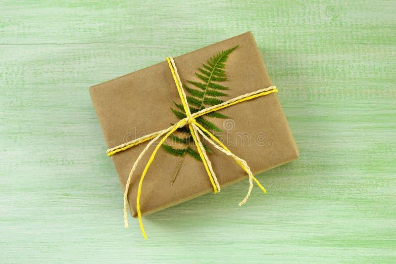 Caixa de presente envolvida do papel do ofício e da fita branca e amarela com folha da samambaia em um fundo de madeira verde imagens de stock
