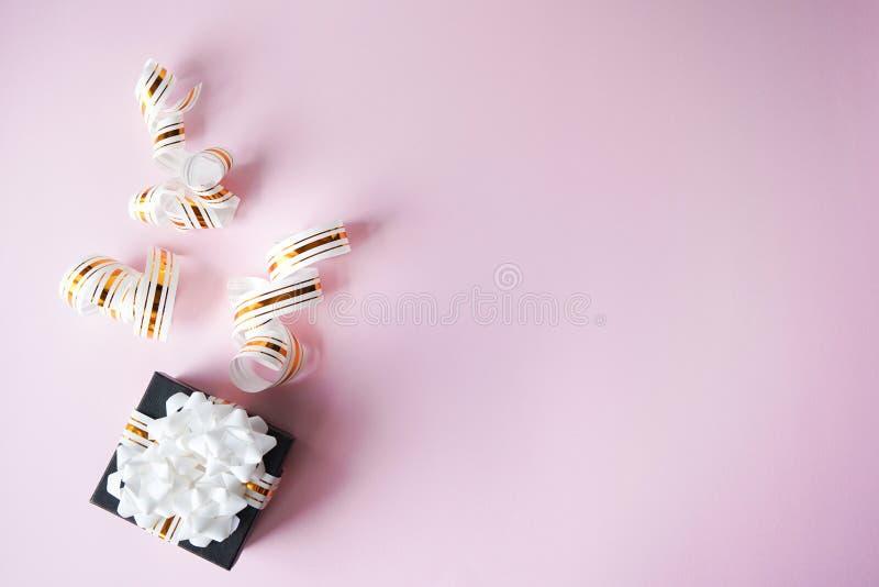 A caixa de presente envolvida em branco e no ouro listrou a fita no fundo cor-de-rosa pastel Copie o espa?o presente para o Natal imagens de stock