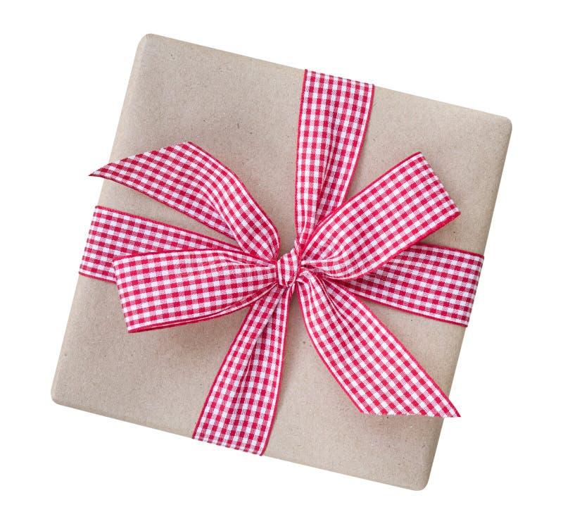 A caixa de presente envolvida no marrom reciclou o papel com ging vermelho e branco imagem de stock
