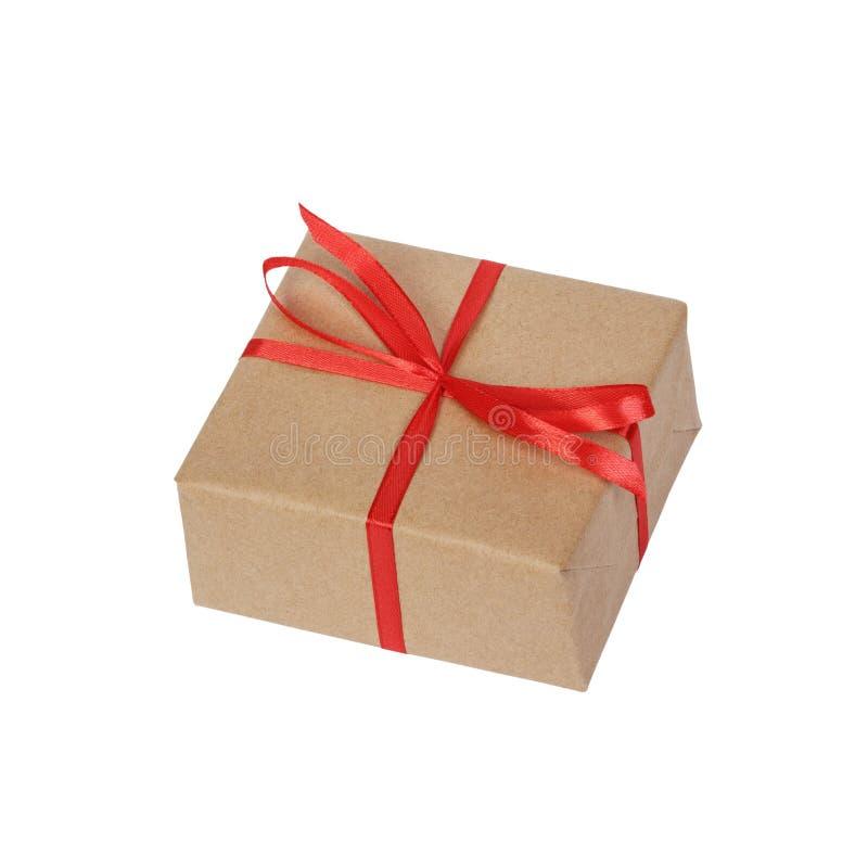 A caixa de presente envolvida no marrom reciclou o papel com opinião superior da curva vermelha da fita isolado no fundo branco,  imagens de stock royalty free