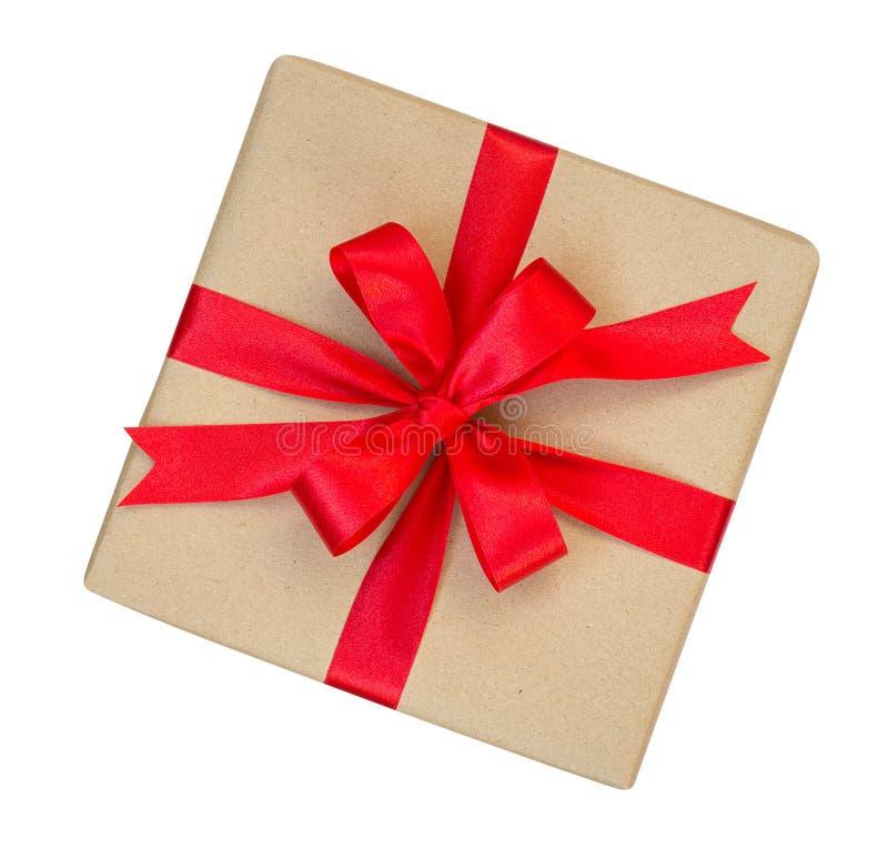 A caixa de presente envolvida no marrom reciclou o papel com parte superior vermelha da curva da fita fotografia de stock