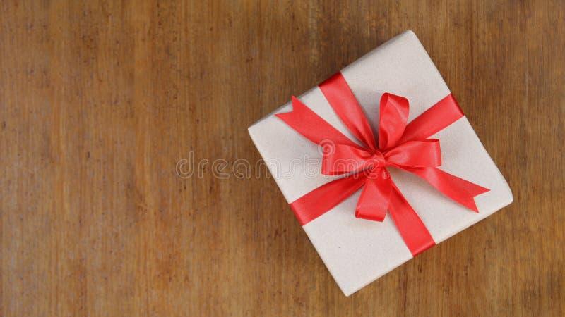 A caixa de presente envolvida no marrom reciclou o papel com parte superior vermelha da curva da fita foto de stock royalty free