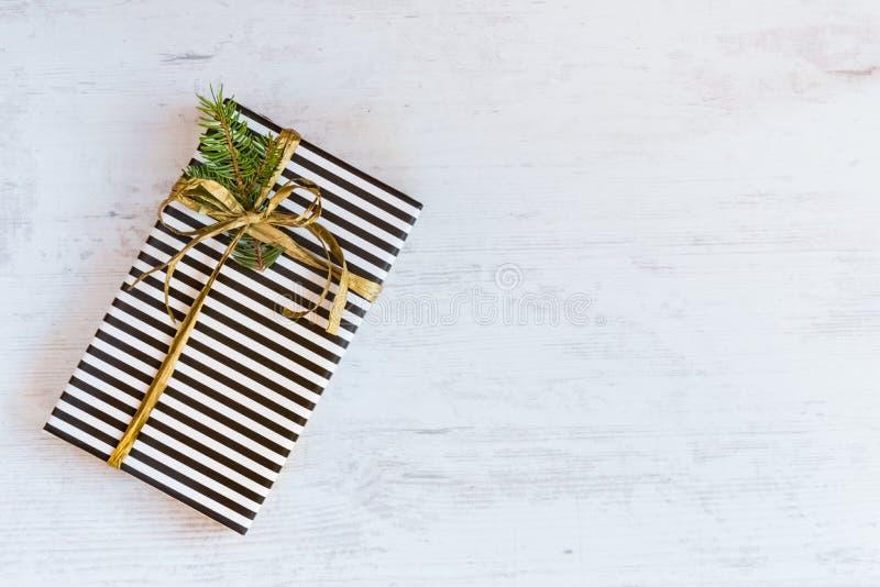 A caixa de presente envolvida no papel listrado preto e branco com fita dourada e o abeto ramificam em um fundo de madeira branco fotos de stock royalty free