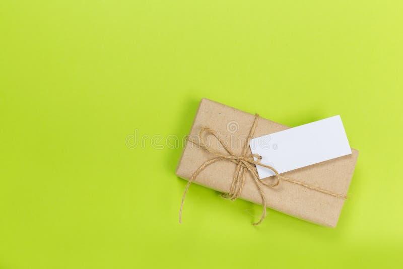 Caixa de presente envolvida no papel reciclado com curva da fita na superfície verde imagens de stock royalty free