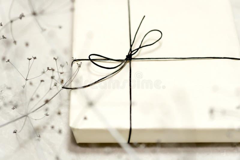 Caixa de presente feita do papel de embalagem, amarrado com laço Um coração vermelho de madeira imagens de stock