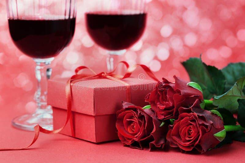 Caixa de presente, flores das rosas vermelhas e dois vidros do vinho imagens de stock royalty free