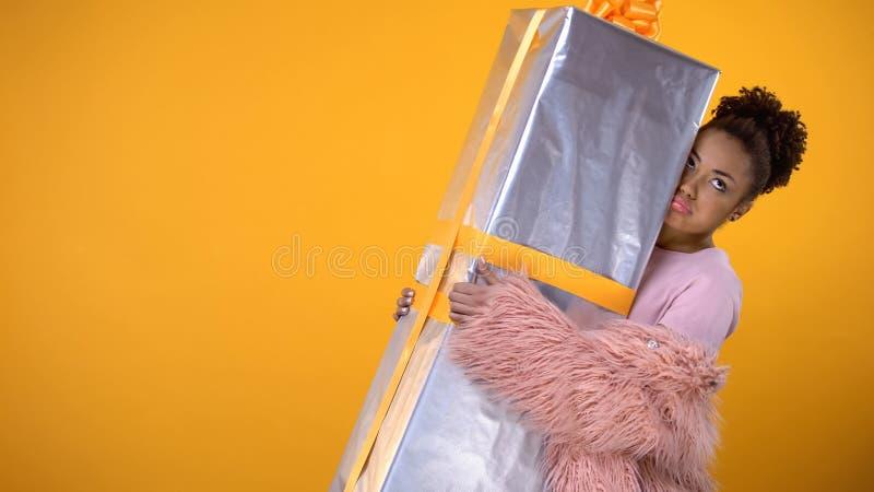 Caixa de presente grande levando fêmea afro-americana, vendas do feriado e bônus, entrega fotografia de stock