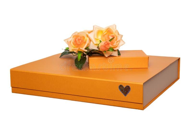 Caixa de presente isolada O close-up de uma caixa de presente dourada grande e pequena com um ramalhete de rosas alaranjadas boni fotografia de stock royalty free
