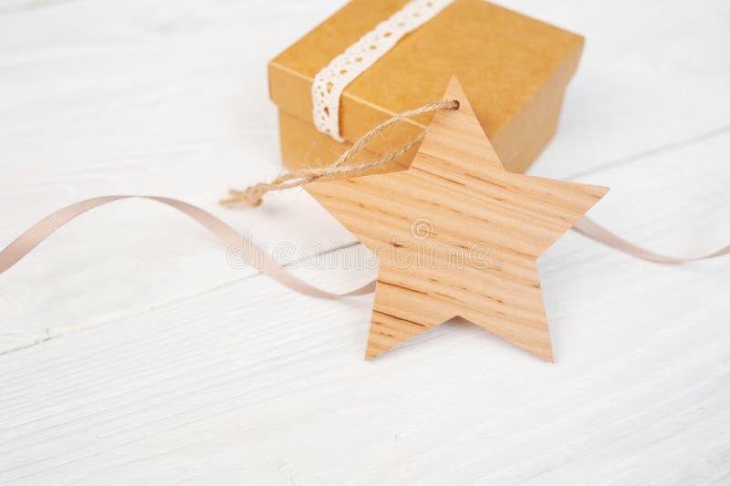 Caixa de presente de kraft do Natal do modelo com a estrela de madeira do xmas no fundo de madeira Vista superior para o cartão c imagem de stock