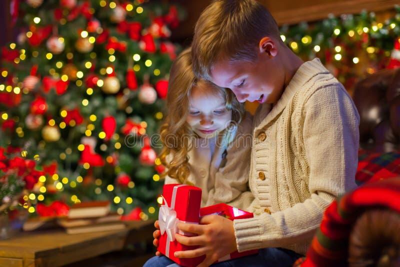 Caixa de presente mágica do Natal crianças no sofá em uma obscuridade acolhedor imagem de stock