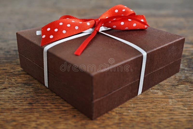 A caixa de presente marrom pequena envolvida com fita branca e vermelho pontilhou a curva no fundo de madeira como um símbolo da  fotos de stock royalty free