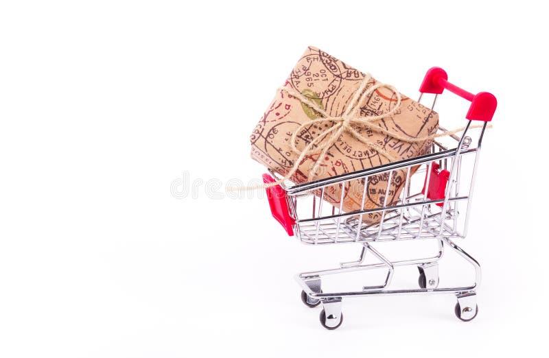 Caixa de presente no carrinho de compras no fundo branco Trole da loja Discontos e presentes imagens de stock