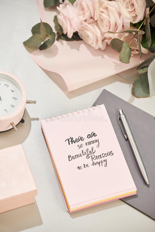 A caixa de presente, o despertador e o rosa aumentaram flores na opinião de tampo da mesa branca no estilo colocado liso Cartão p fotos de stock royalty free